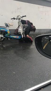 下雨天骑车小心!小姐姐雨衣被卷入车轮,狠狠地摔了一跤